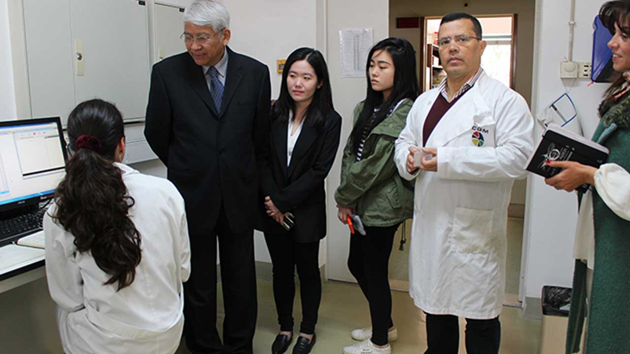 Rector of the City University of Macau talking with junior CQM researcher Fátima Mendes.